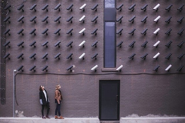 people looking up at many surveillance cameras